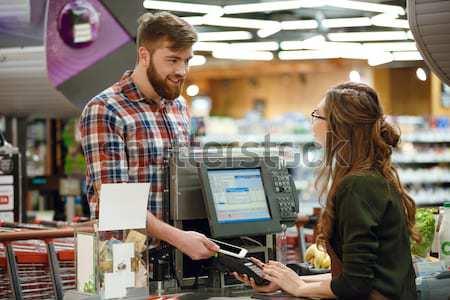 счастливым молодым человеком Постоянный столе супермаркета изображение Сток-фото © deandrobot