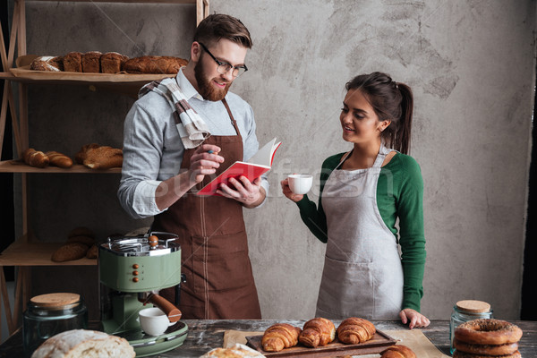 Cheerful loving couple bakers drinking coffee looking at notebook. Stock photo © deandrobot
