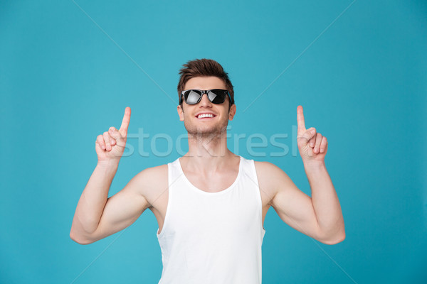 Cheerful young guy in sunglasses pointing Stock photo © deandrobot
