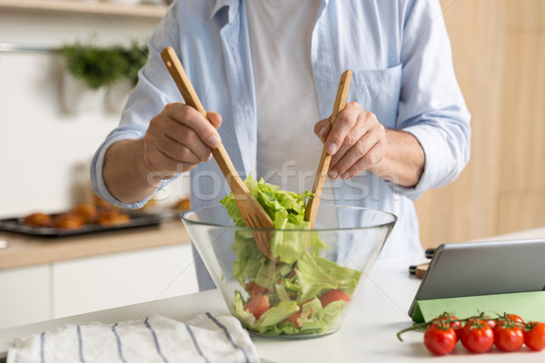 Cropped photo of mature man cooking salad Stock photo © deandrobot