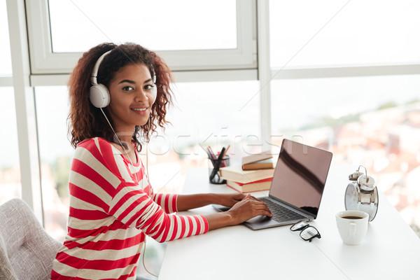 Gülen Afrika kadın dizüstü bilgisayar kullanıyorsanız işyeri dinleme Stok fotoğraf © deandrobot
