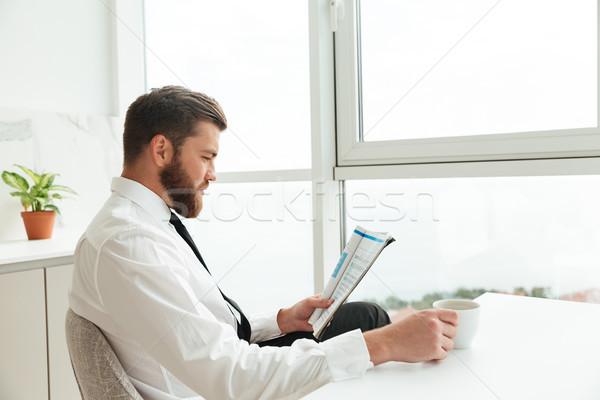 Zijaanzicht bebaarde man business kleding lezing Stockfoto © deandrobot