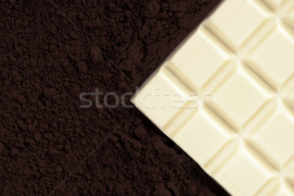 Close-up of a white chocolate bar over milk chocolate powder Stock photo © deandrobot