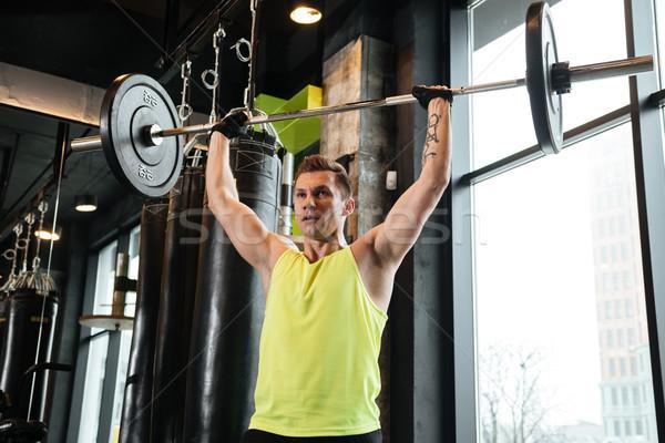 Handsome sportsman make sport exercises in gym. Stock photo © deandrobot