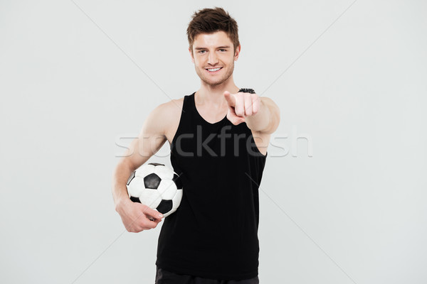 Cheerful young sportsman with foot ball pointing. Stock photo © deandrobot