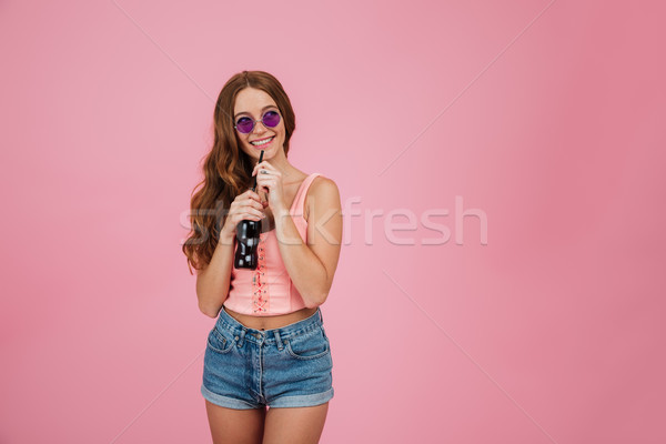 Young woman in sunglasses and summer clothes drinking fizzy drink Stock photo © deandrobot