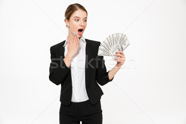 Shocked blonde business woman holding money and looking on their Stock photo © deandrobot