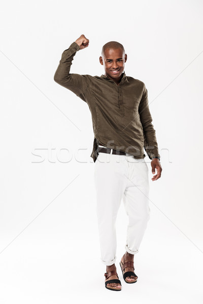 Full length image of Strong african man showing his bicep Stock photo © deandrobot