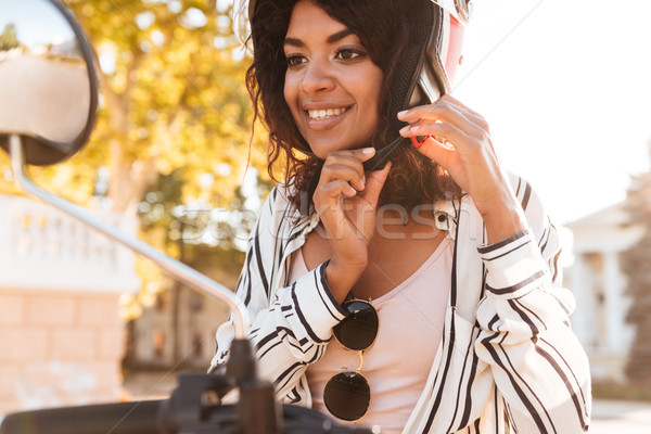 Close-up image of happy african woman sitting on modern motorbike Stock photo © deandrobot