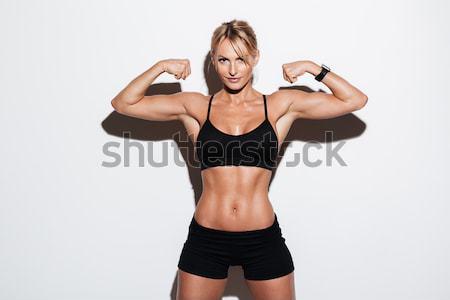 Portrait of a confident muscular sportswoman Stock photo © deandrobot