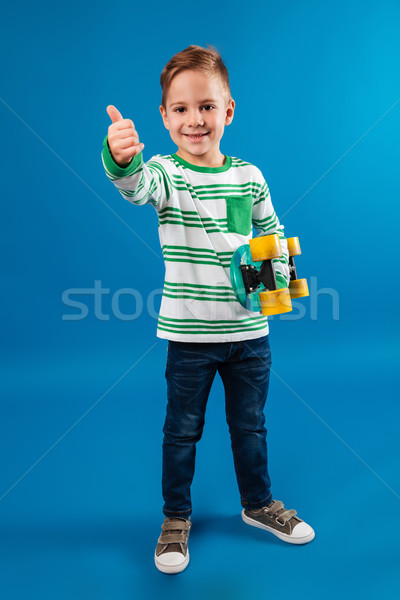 Full length image of smiling young boy holding skateboard Stock photo © deandrobot