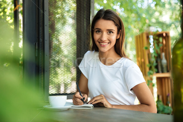 Portrait of a smiling beautiful girl making notes Stock photo © deandrobot