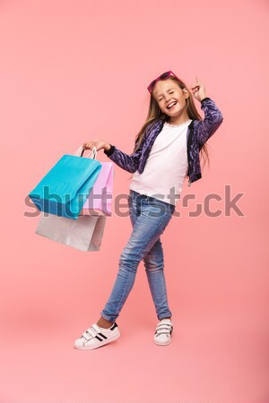 Full length image of shocked blonde woman moving with packages Stock photo © deandrobot
