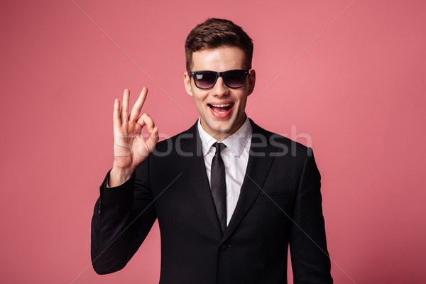 Cheerful man showing ok gesture and smiling to camera Stock photo © deandrobot