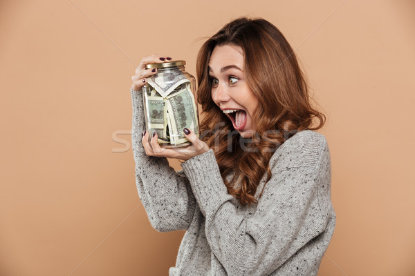 Overjoyed curly brunette girl holding glass jar with her savings Stock photo © deandrobot