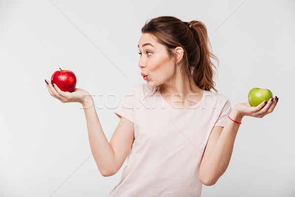 Portrait of a cheery happy girl holding apples Stock photo © deandrobot