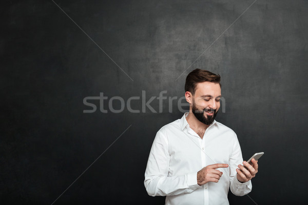 Content smiling man in white shirt typing text message or scroll Stock photo © deandrobot