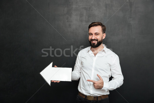 Photo of unshaved man smiling and holding blank speech arrow poi Stock photo © deandrobot