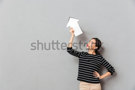 Portrait of a pretty woman pointing away Stock photo © deandrobot