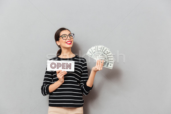 Portrait of a satisfied woman in eyeglasses holding open sign Stock photo © deandrobot