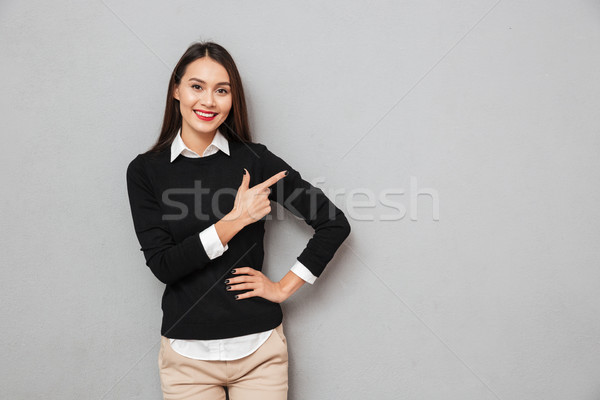 Smiling asian woman in business clothes with arm on hip Stock photo © deandrobot