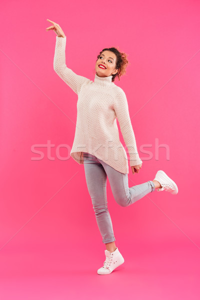 Full length portrait of a cheerful girl pointing finger away Stock photo © deandrobot