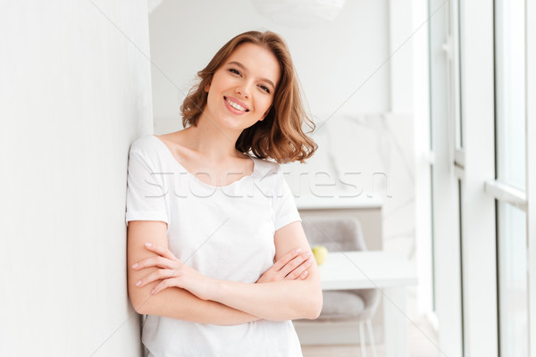 Happy young woman standing near window with arms crossed Stock photo © deandrobot