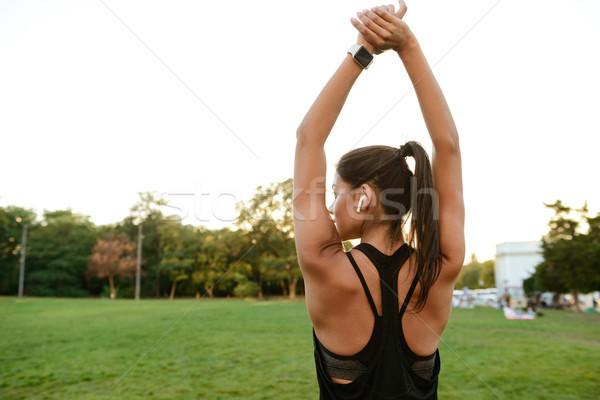 Hátulnézet portré fitnessz nő fülhallgató nyújtás kezek Stock fotó © deandrobot