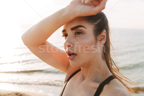 Close up portrait of a tired young sportswoman wiping Stock photo © deandrobot