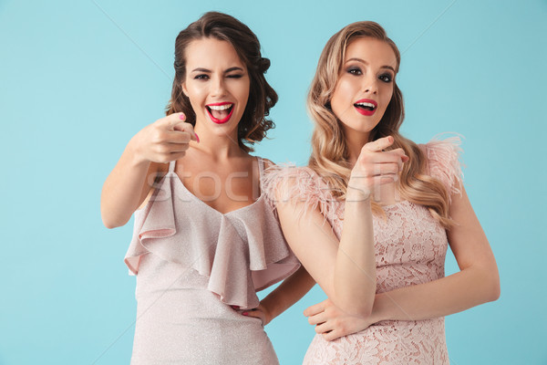 Two adorable girls 20s wearing party outfit pointing index finge Stock photo © deandrobot