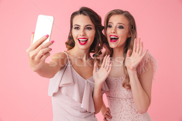 Photo of two young party women 20s taking selfie photo on mobile Stock photo © deandrobot
