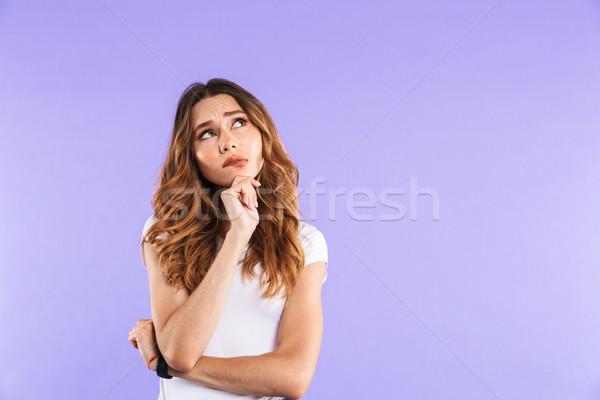 Portré töprengő fiatal lány áll izolált ibolya Stock fotó © deandrobot
