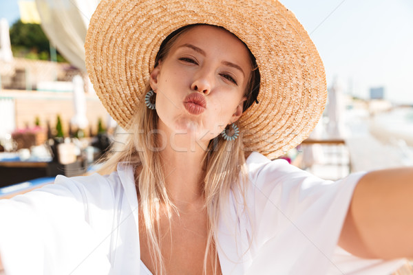 Photo closeup of caucasian blond woman 20s in straw hat and swim Stock photo © deandrobot