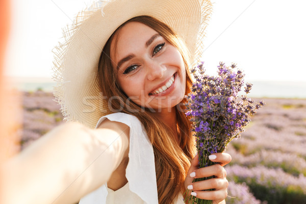 Lovely young girl in straw hat holding lavender bouquet Stock photo © deandrobot