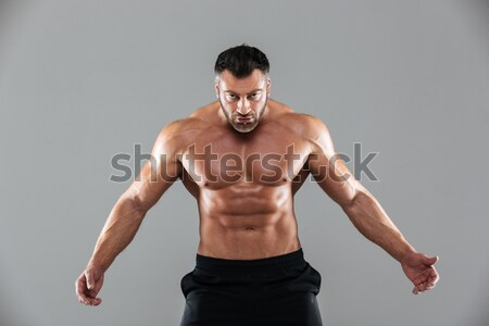 Portrait of a muscular man with nice abs over gray background Stock photo © deandrobot