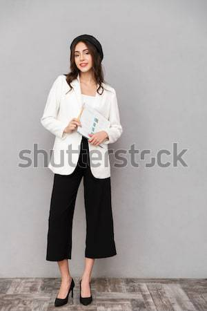 Happy woman standing and looking away over gray background Stock photo © deandrobot