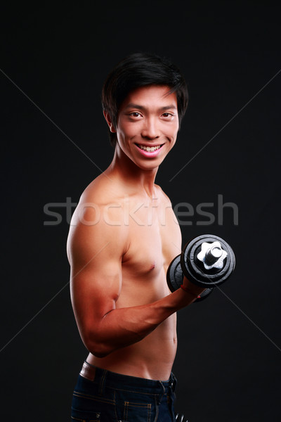 Smiling asian man working out with dumbbell on black backgroung Stock photo © deandrobot