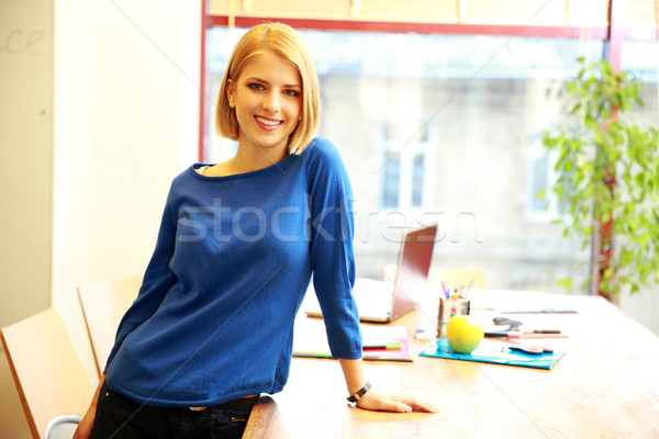 Young happy woman leaning on the table at office Stock photo © deandrobot