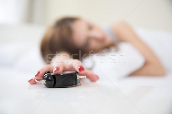 Schläfrig Frau Bett Hand Wecker Schwerpunkt Stock foto © deandrobot