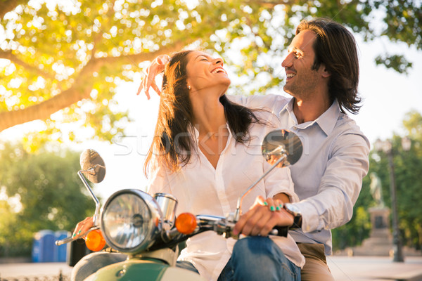 Laughing european couple flirting on scooter Stock photo © deandrobot
