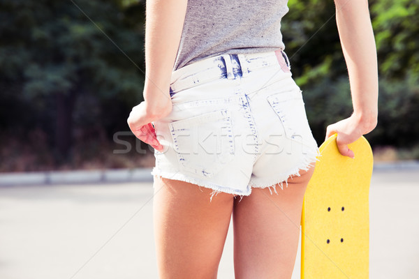Female ass in shorts with skateboards outdoors Stock photo © deandrobot