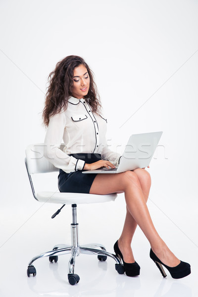 Souriant femme d'affaires utilisant un ordinateur portable chaise de bureau portrait isolé Photo stock © deandrobot