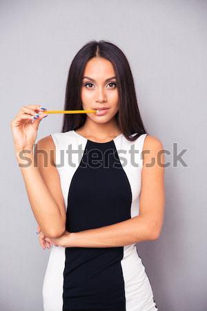 Female model posing over gray background Stock photo © deandrobot