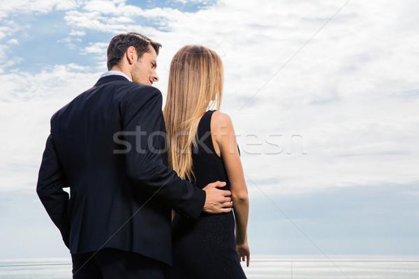 Back view portrait of romantic couple hugging Stock photo © deandrobot