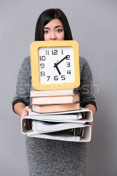 Woman holding books, folders and wall clock Stock photo © deandrobot