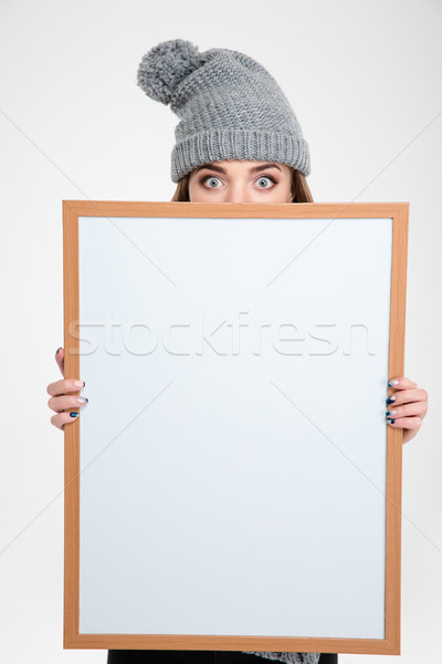 Woman in hat peeping over blank board Stock photo © deandrobot