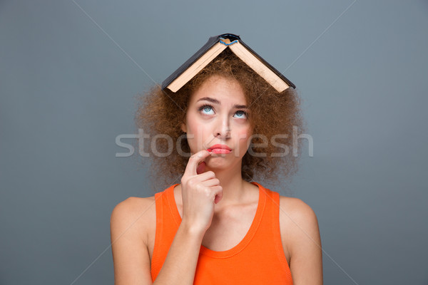 Curly annoyed woman looking funny with book on head Stock photo © deandrobot