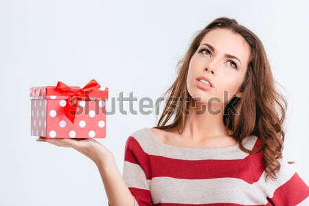 Happy thoughtful woman holding gift box and looking up Stock photo © deandrobot