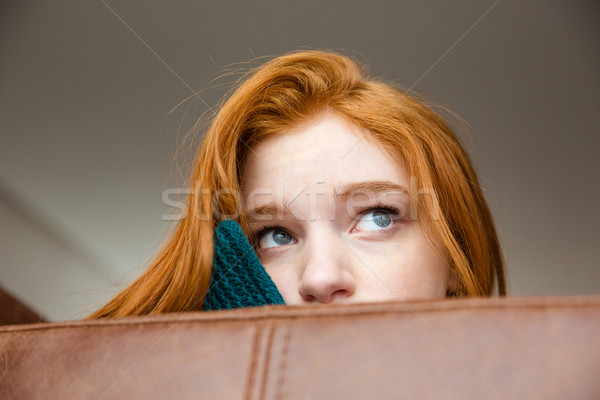 Unconfident shy redhead girl peeping from sofa  Stock photo © deandrobot