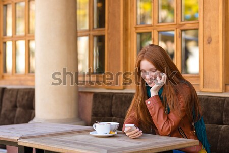 Pretty thoughtful girl with red hair drinking coffee outdoor Stock photo © deandrobot